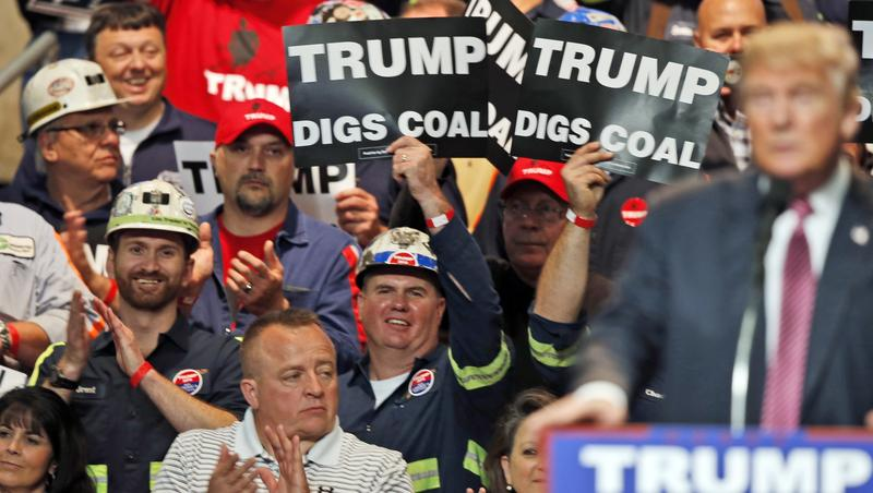Coal miners wave signs as then-presidential candidate Donald Trump speaks during a rally, Charleston, WV, May 5, 2016