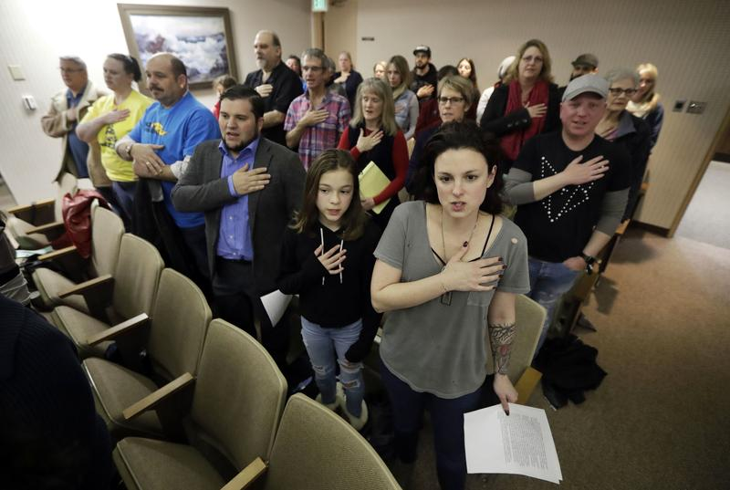 Members of the Orchard City Indivisible Group raise their hands in support of a fellow member who spoke before the city's council against the policies of President Trump Tuesday, March 7, 2017.