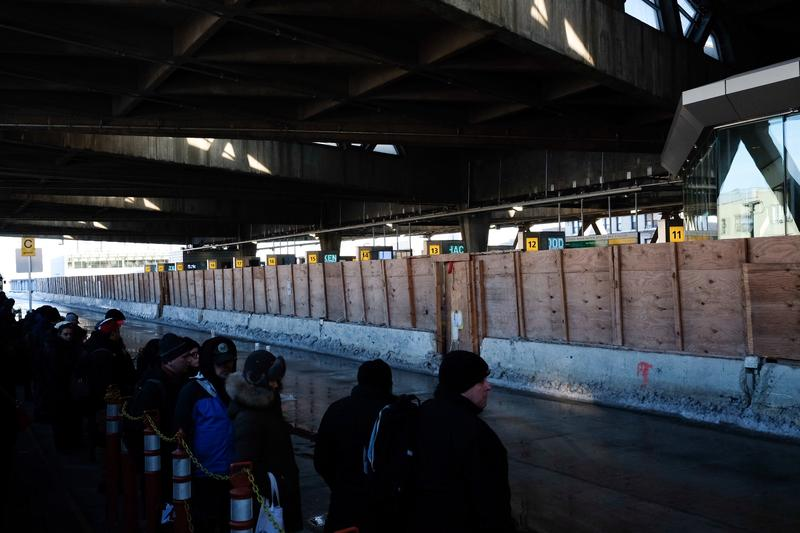 Commuters wait on the upper level of the George Washington Bridge  Terminal for buses to New Jersey while the terminal behind them remind under  construction. (Stephen Nessen/WNYC)