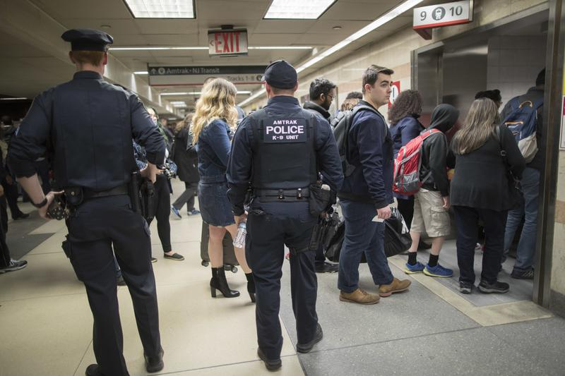 Amtrak police watch as passengers make their way to the track to board the first train to leave Penn Station after delays caused by a stuck train, Friday, April 14, 2017.