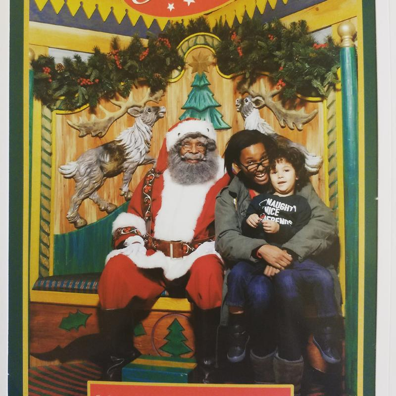Sa'iyda Shabazz and her son pose with the black Santa at Macy's Herald Square store