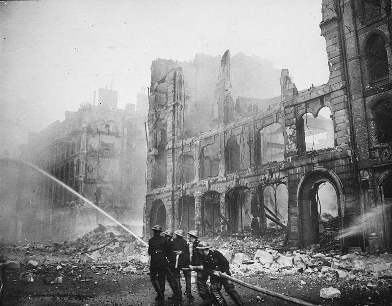 Firefighters tackling a blaze amongst ruined buildings after an air raid on London.