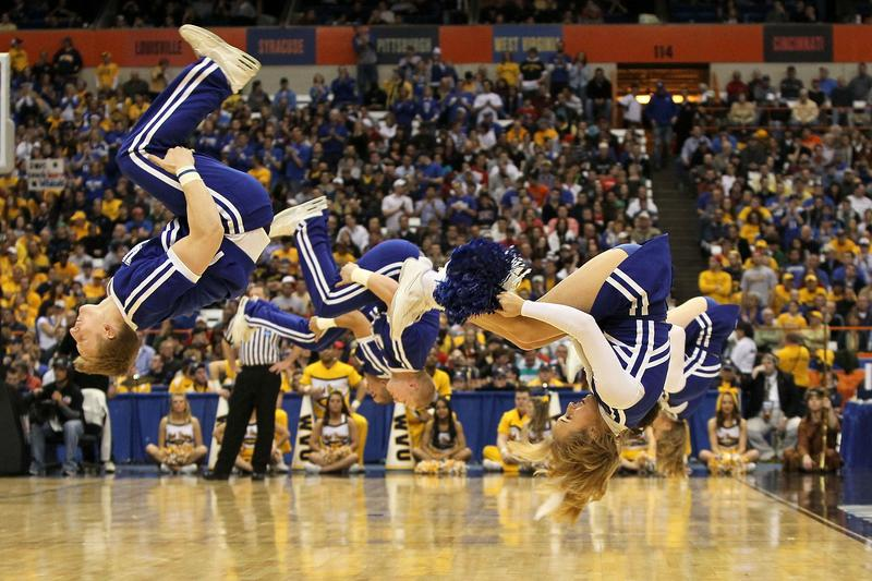 College cheerleaders perform stunts.