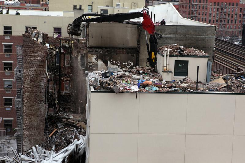 Cranes knock down the remaining wall of one of the two buildings that were destroyed in East Harlem after a gas explosion.