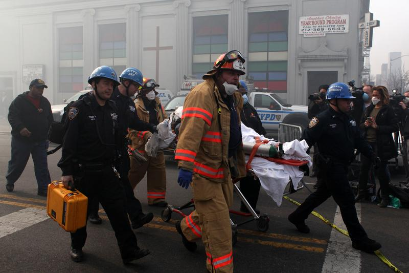 Emergency personnel carry people away from the site of a 5-alarm fire in the Bronx after two buildings exploded in East Harlem on March 12, 2014.