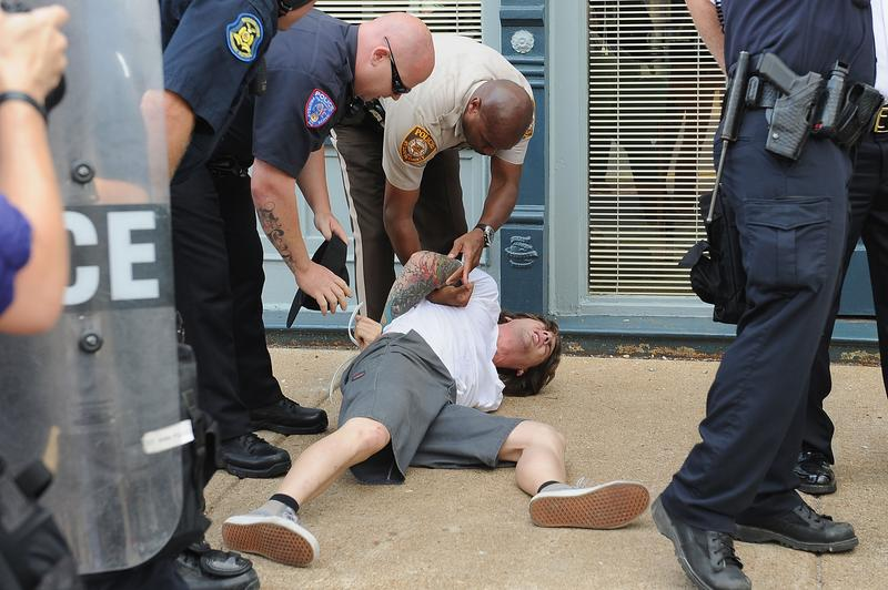 A man is arrested during a protest of the shooting death of 18-year-old Michael Brown outside Ferguson Police Department Headquarters August 11, 2014 in Ferguson, Missouri.