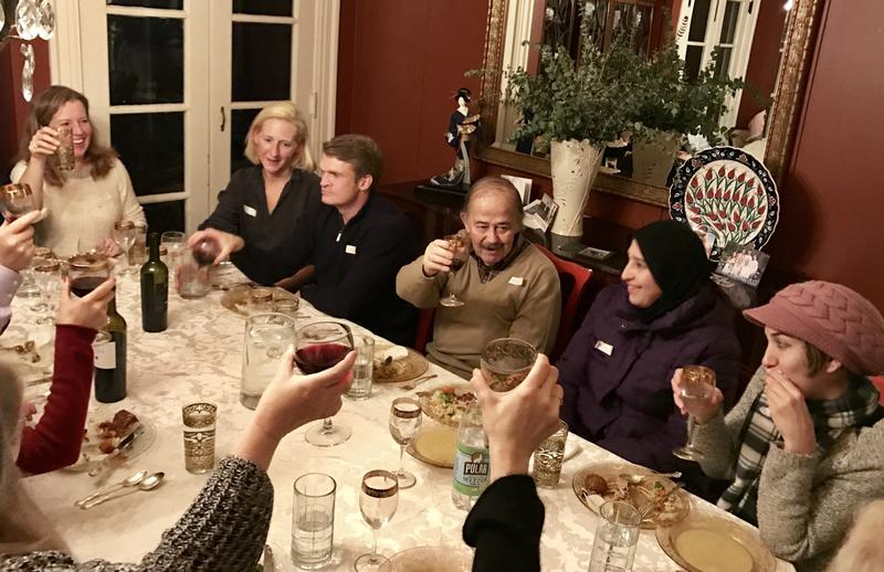 At a dinner of the Syria Supper Club in Maplewood, NJ, last month, guests raise a glass to Khlood Al Nabelsi (center), a Syrian refugee who cooked a banquet-style feast.Host Kate McCaffrey is at left.