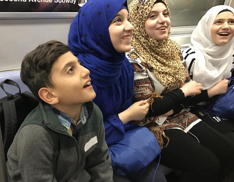 Syrian refugees on their first subway ride in New York City.