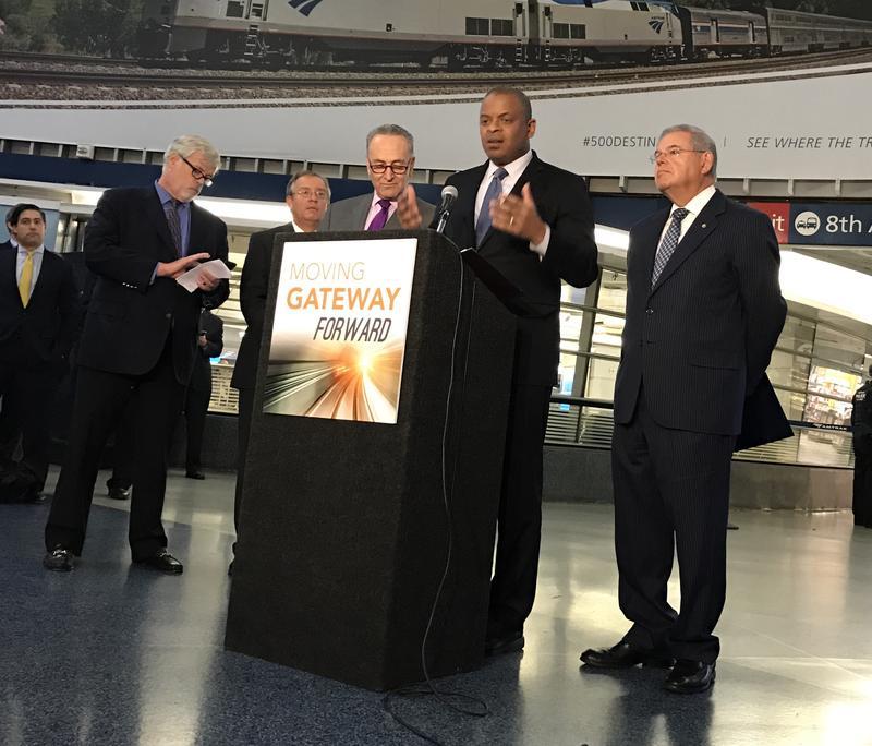U.S Transportation Secretary Anthony Foxx (at podium) flanked by Senators Charles Schumer (L) and Robert Menendez (R)