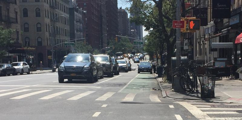 A car driving in a protected bike lane on Amsterdam Avenue