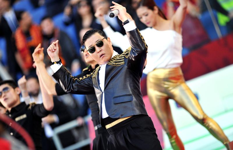Korean pop artist Park Jae Sang (C), popularly known as 'Psy', sings as he performs his 'Gangnam Style' song