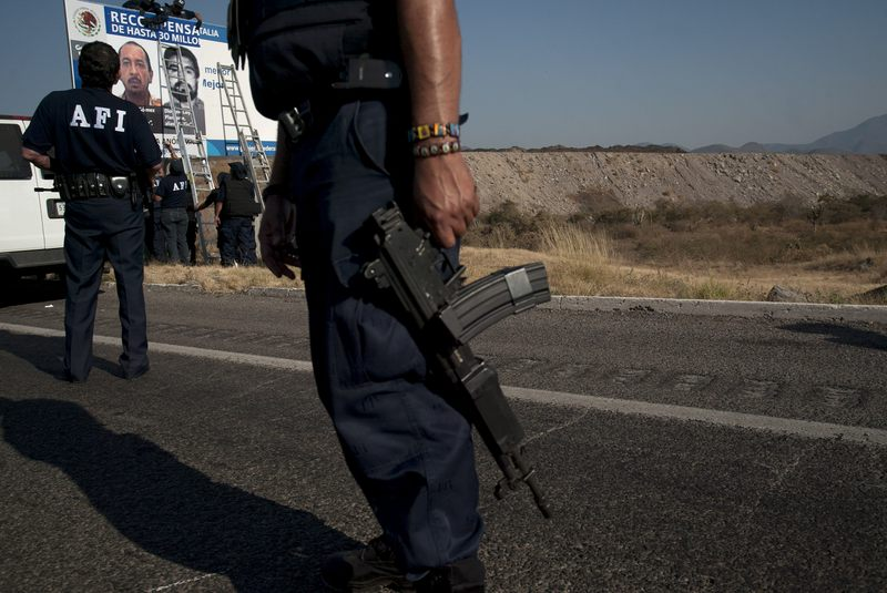 Soldiers and Federal Police officers install a checkpoint on a road inside the zone of influence of La Familia drug cartel on December 12, 2010 in Apatzingan, Mexico.