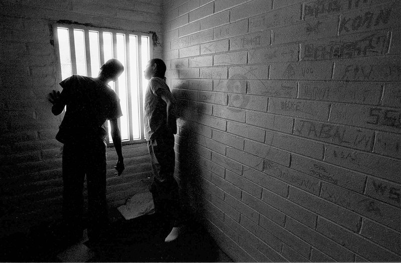 Two juveniles look out of a cell at the Bisbee Juvenile Detention Center in Bisbee, Arizona, November 15 1995.