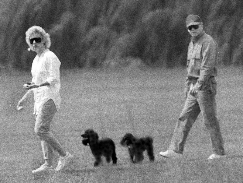 Whitey Bulger and Catherine Greig walk together with Greig's poodles underfoot.