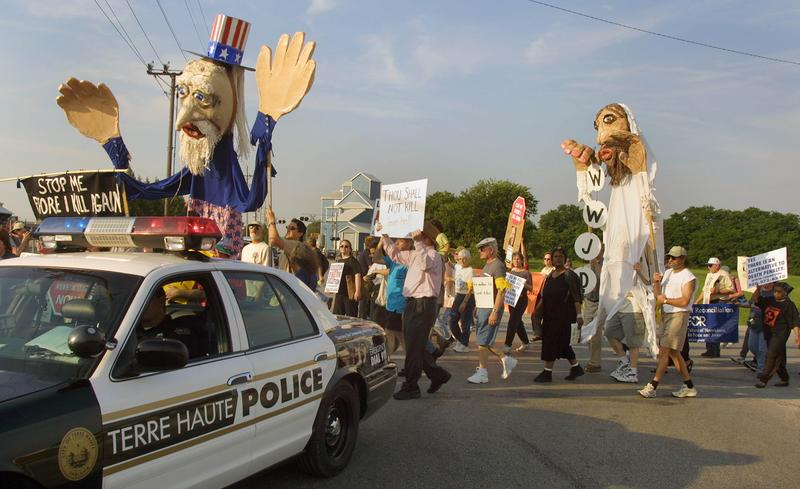 A police car precedes a political demonstration in Terre Haute, Indiana.