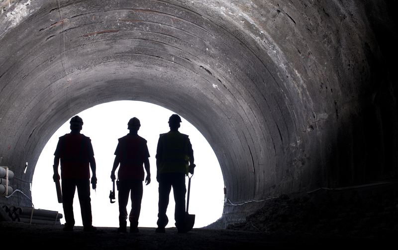 Silhouette of workers in tunnel