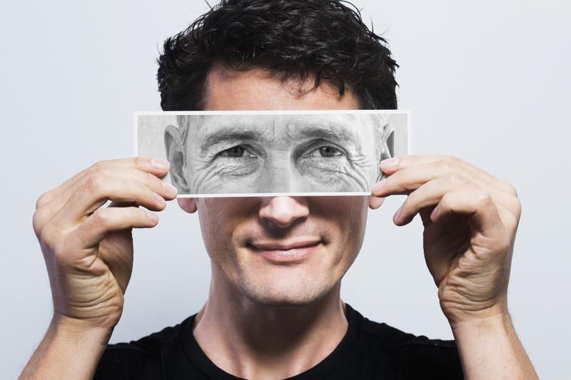 Young man holding picture of old eyes over his eyes.