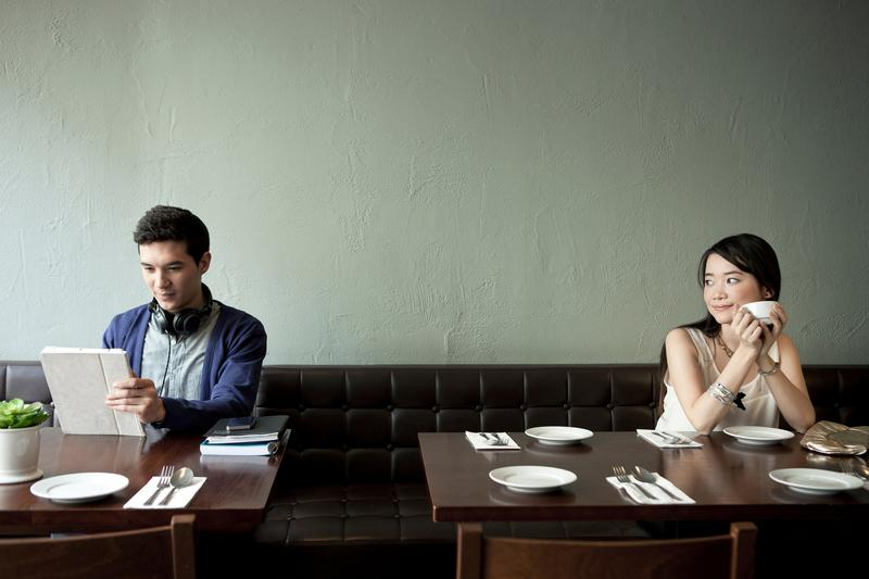Young woman looking at young man in restaurant.