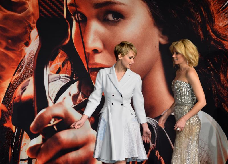Jennifer Lawrence and Elizabeth Banks arrive on the red carpet for the German premiere of the film 'The Hunger Games: Catching Fire' in Berlin on November 12, 2013.