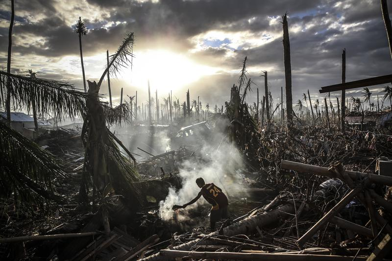 A man fans flames on a fire Tanauan on November 19, 2013 in Leyte, Philippines. Typhoon Haiyan ripped through Philippines, leaving thousands dead and hundreds of thousands homeless.