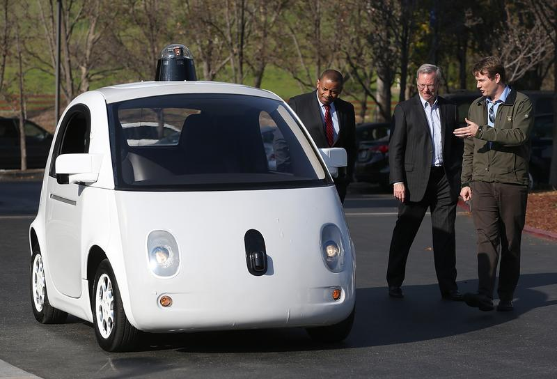 Google's Chris Urmson (R) shows a Google self-driving car to U.S. Transportation Secretary Anthony Foxx (L) and Google Chairman Eric Schmidt (C) at the Google headquarters on February 2, 2015.