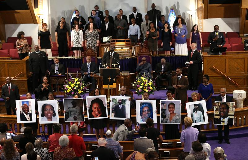 Photographs of the nine victims killed at the Emanuel African Methodist Episcopal Church in Charleston, South Carolina are held up by congregants during a prayer vigil on June 19, 2015.