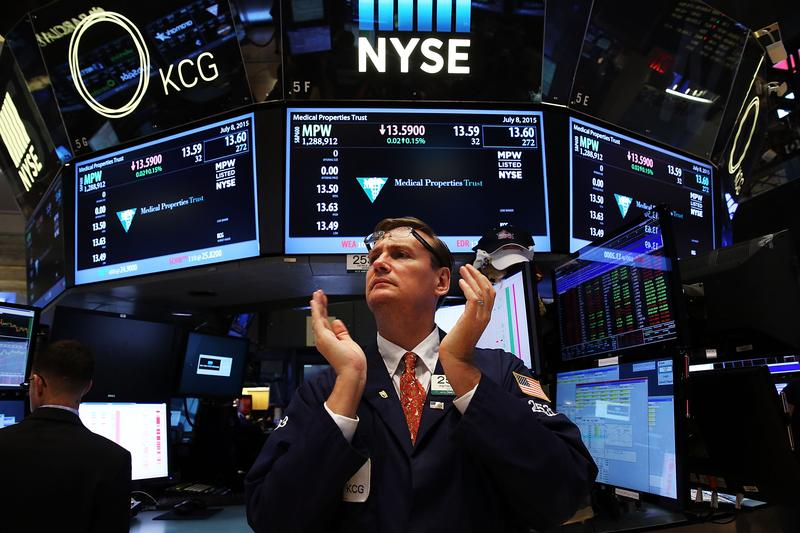 A trader claps on the floor of the New York Stock Exchange (NYSE) at the close of the day after trading was paused for nearly four hours due to a 'technical glitch' on July 8, 2015 in New York City.