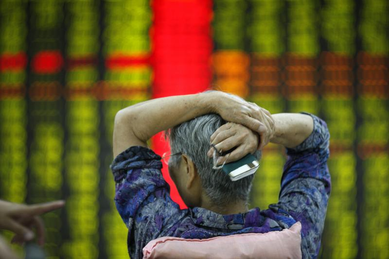 An investor watches market returns at a stock exchange hall   in Tai an, China. Chinese shares dropped sharply on Monday.
