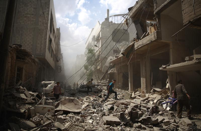 Syrians walk amid the rubble of destroyed buildings following reported air strikes by regime forces in the rebel-held area of Douma, east of the capital Damascus, on August 30, 2015.