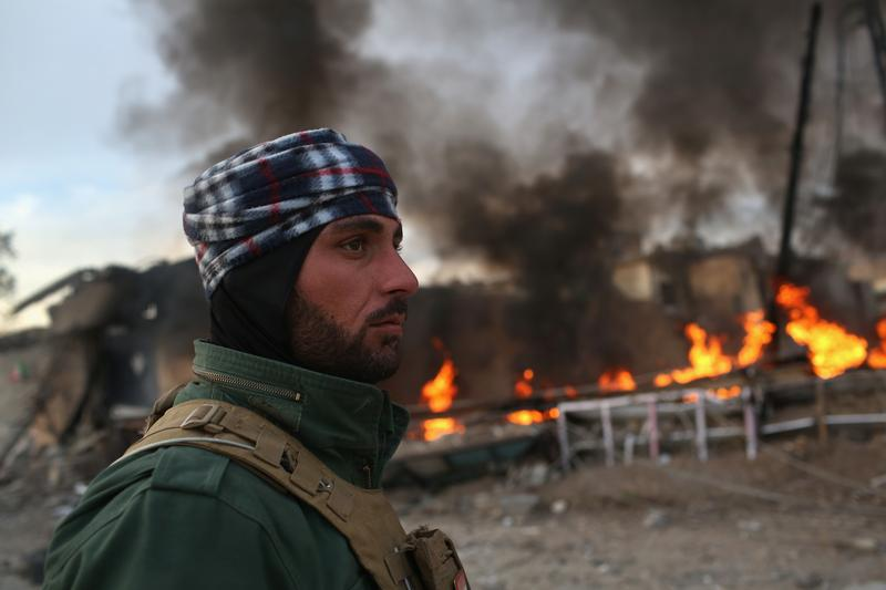 A Kurdish Peshmerga soldier passes by tires set afire days before by ISIL extremists to hinder airstrikesSinjar, Iraq.