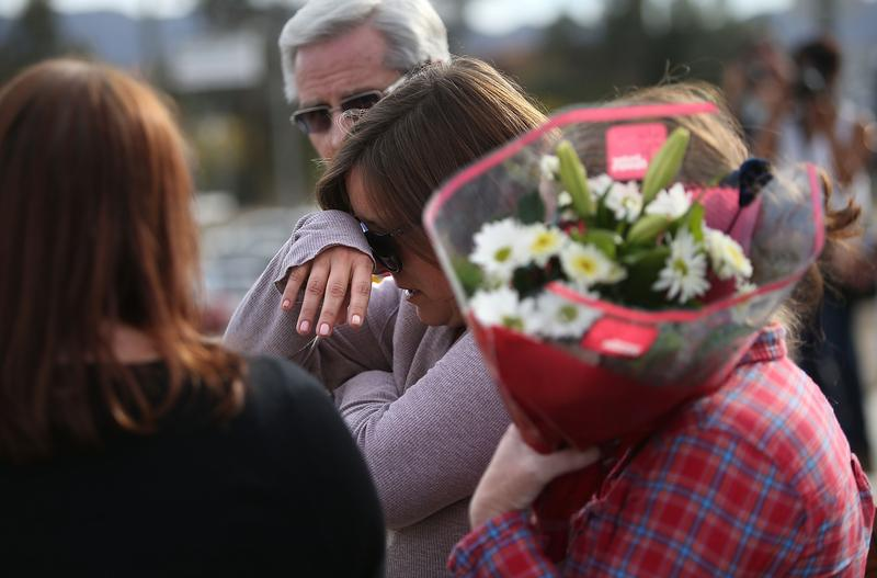 A mourner cries as she brings flowers to a road block outside of the Inland Regional Center on December 3, 2015 in San Bernardino, California.