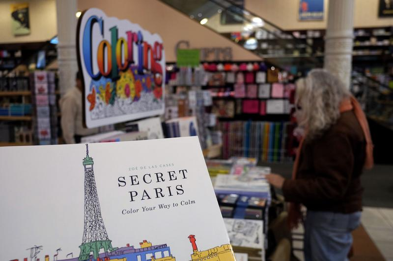 A woman checks out coloring pencils next to adult coloring books at a Barnes and Nobel store in New York.
