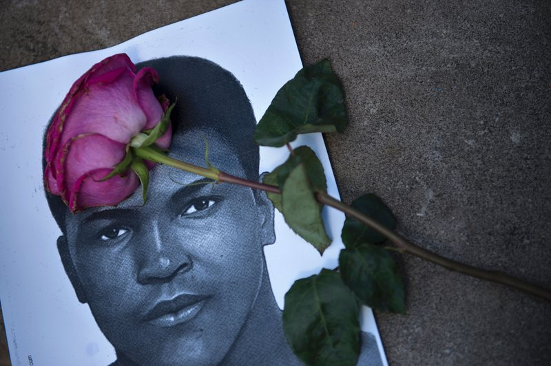 A flower and a image of Muhammad Ali are seen as people leave items to pay their respects to boxing legend Muhammad Ali at the Muhammad Ali Center June 5, 2016 in Louisville, Kentucky.
