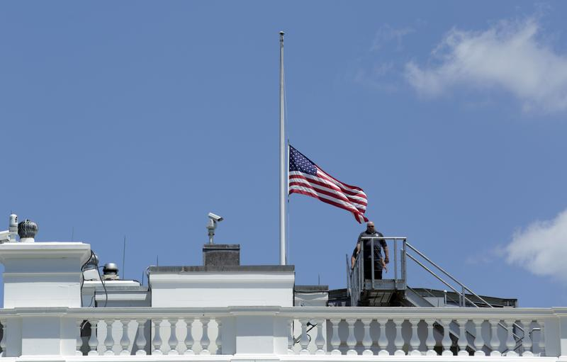 Personnel leave after lowering the US flag to half-staff at the the White House in Washington following President Obama's statement on the mass shooting at an Orlando nightclub.