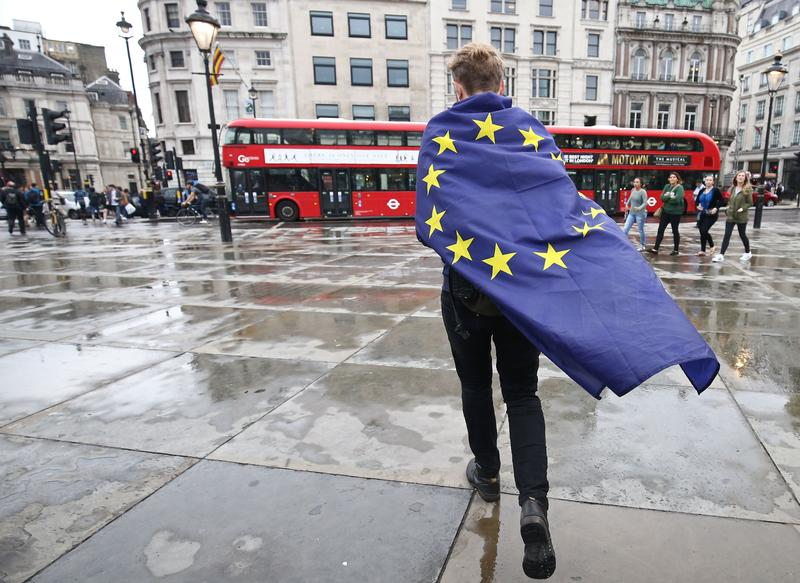 A demonstrator wrapped in a European flag leaves an anti-Brexit protest in Trafalgar Square in central London on June 28, 2016.