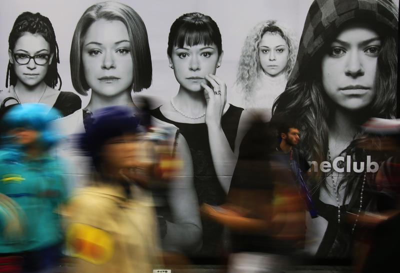 Fans pass by BBC America's Orphan Black ad on a convention hall wall during Comic-Con International in San Diego, July 26, 2014.