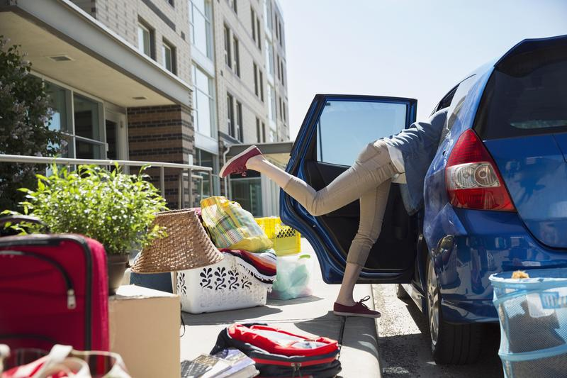 College student reaching in car moving into dorm.
