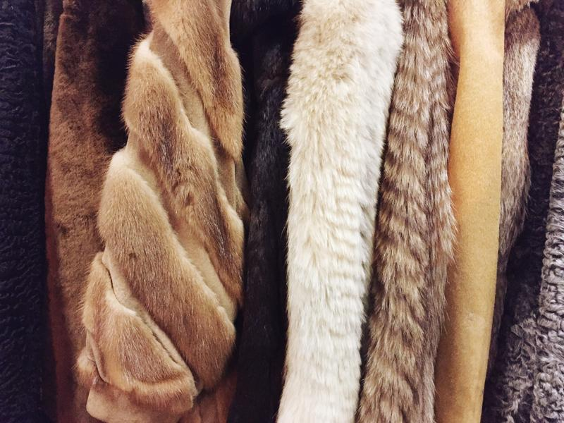 A varied selection of luxury fur coats hangs on the rack