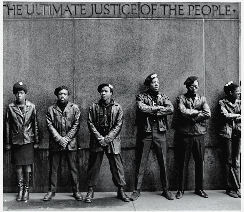 A line of Black Panther Party members as they stand outside the New York City courthouse under a portion of an Abraham Lincoln quote which reads 'The Ultimate Justice of the People.' April 11, 1969