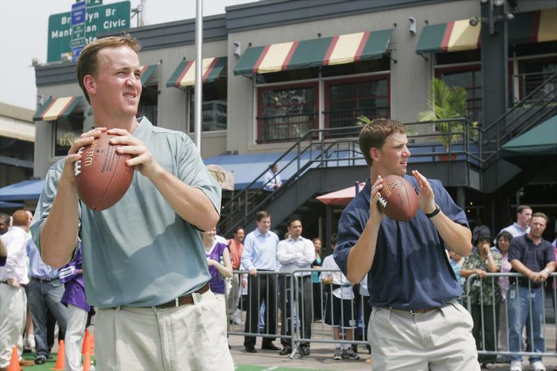 Indianapolis Colts' quarterback Peyton Manning (left) and New York Giants' quarterback Eli Manning pass footballs to fans as they kick off the Yahoo Sports Fantasy Football at South Street Seaport.