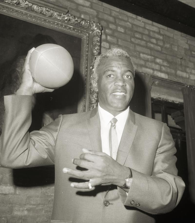 Jackie Robinson, named General Manager of the Brooklyn Dodgers football team, poses with a football on May 3, 1966 in the Brooklyn borough of New York City.