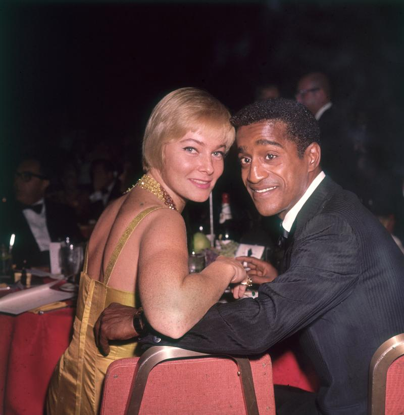 American actor and singer Sammy Davis Jr (1925 - 1990) and his wife, Swedish actor May Britt, smile over their shoulders while sitting at a table at a formal dinner, circa 1965.
