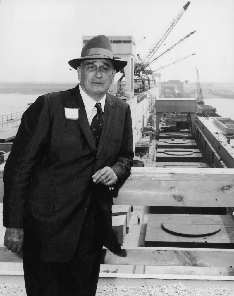 New York City parks commissioner Robert Moses in 1958 stands and leans on a wooden railing in front of a waterfront project site, New York City. Winches are lined up behind him.