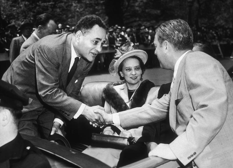 American politician and United Nations official Ralph Bunche shakes hands with New York City Mayor Paul O'Dwyer from his motorcade while his wife, Ruth Bunche looks on, New York City, May 17, 1949.