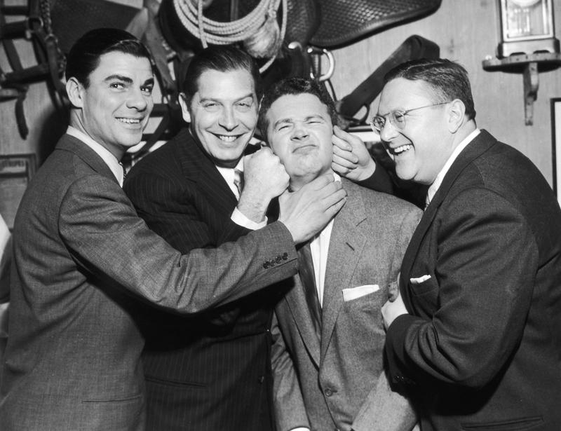 American television hosts Bert Parks (L) and Sam Levinson (R) along with American comic actor Milton Berle (1908 - 2002) pretend to beat up American comic actor Red Buttons (2nd from R).