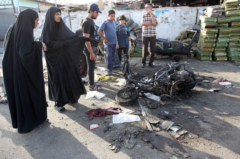 Iraqi onlookers gather on July 16, 2014 around a burnt motorcycle at the scene of an explosion that took place the previous night in Sadr City, one of Baghdad's northern Shiite-majority districts.