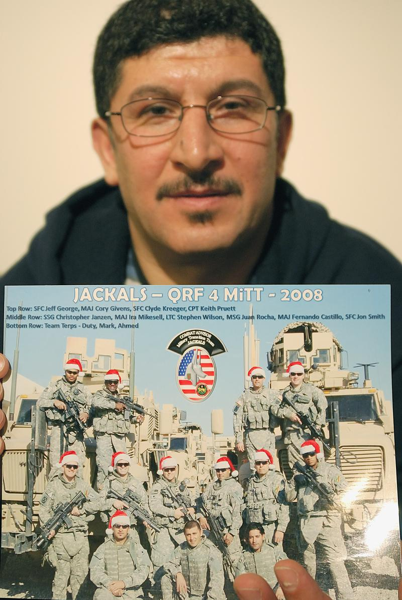 This December 15, 2010, file photo shows Iraqi refugee Ayad Salman in Chicago, Illinois, holding a picture of one of the US units he worked with as a translator in Iraq before fleeing the country.