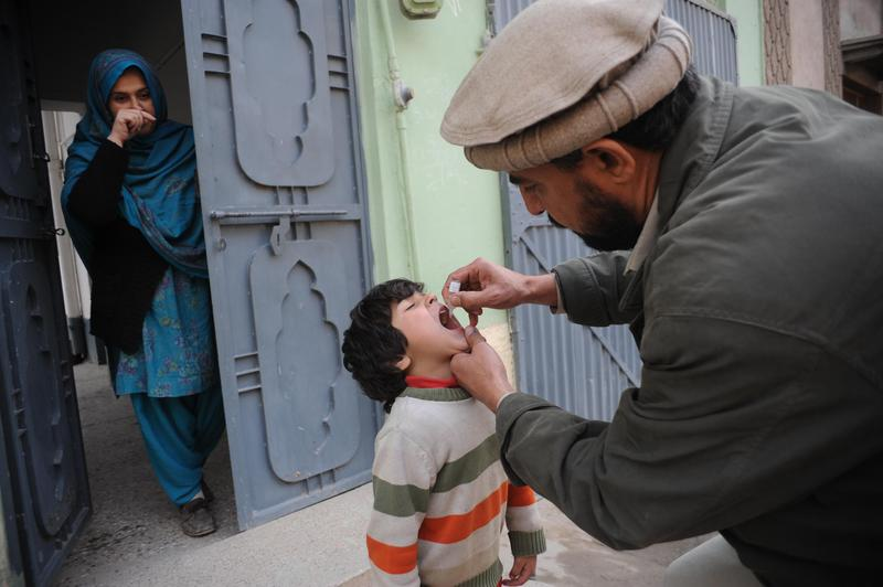 A Pakistani health worker administers a polio vaccination to a child during a polio immunisation campaign in Peshawar on February 2, 2014.