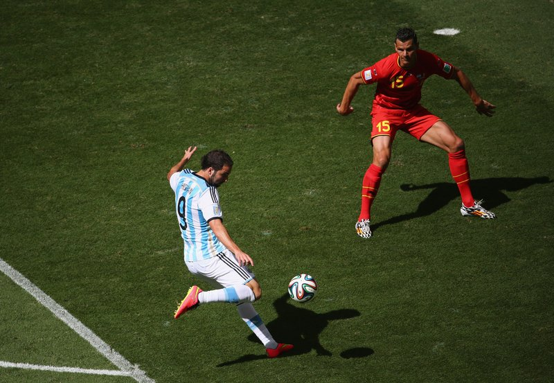 Gonzalo Higuain of Argentina scores against Daniel Van Buyten of Belgium during the 2014 FIFA World Cup Brazil Quarter Final match between at Estadio Nacional on July 5, 2014 in Brasilia, Brazil.
