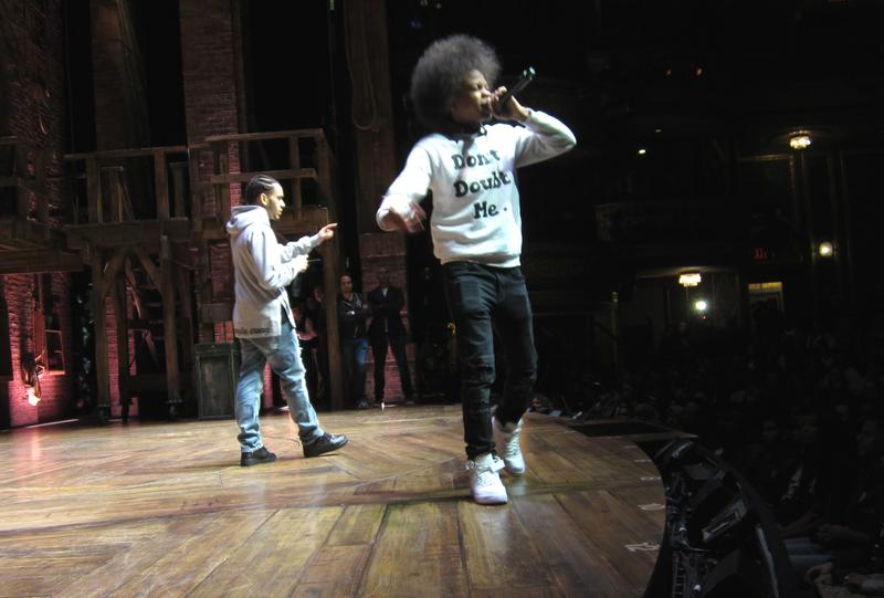 "Nigel Petersen (front) and Jordy Salvador, of the High School for Law and Public Service, performing on the stage of Broadway's ""Hamilton"" before cast members and an audience of teens"